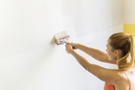 Young woman painting wall at new home - FBAF00031