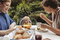 Two happy mothers at breakfast table outdoors with their child - MFF04421