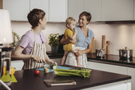 Happy lesbian couple and their child in kitchen - MFF04424