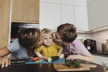 Happy lesbian couple kissing their child in kitchen - MFF04427