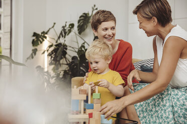 Two mothers learning and playing with their child at home - MFF04433