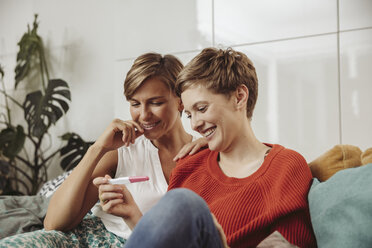 Happy lesbian couple looking at pregnancy test - MFF04439