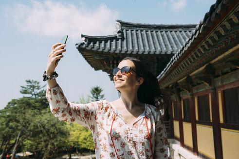 South Korea, Gyeongju, happy woman taking a selfie with cell phone in Bulguksa Temple - GEMF02397