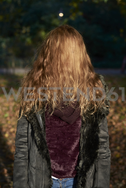 Hair covering face of woman standing in a park - IGGF00524