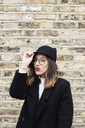 Portrait of fashionable woman with red lips wearing black cap and coat - IGGF00530