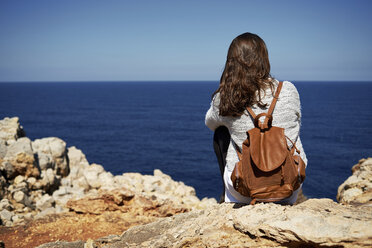 Young brunette woman sitting on coast, looking at view - IGGF00539