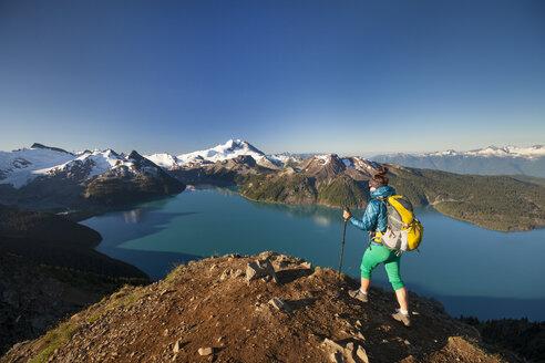 A backpacker reaches the summit of Panorama Ridge in Garibaldi Provincial Park, British Columbia, Canada. - AURF03624