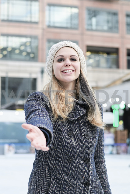 Pretty blond young woman wearing wool cap in winter, reaching out hand - IGGF00552