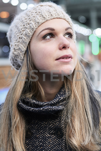 Portrait of pensive blond young woman wearing wool cap in winter - IGGF00555