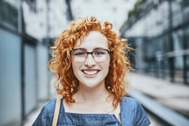 Portrait of a young redheaded woman wearing glasses, smiling - ZEDF01528
