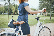 Young woman walking in park, pushing bicycle - ZEDF01534