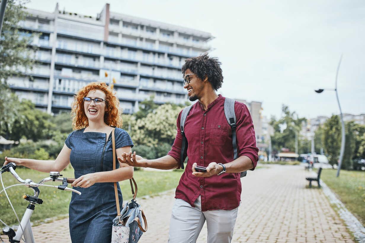 Friends walking in park, talking, woman pushing bicycle - ZEDF01540 - Zeljko Dangubic/Westend61