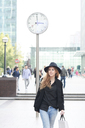 Mid adult woman wearing a hat going shopping in the city - IGGF00561