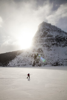 A woman skiing on Two Medicine Lake in front of Sinopah Mountain in Glacier National Park, Montana. - AURF03801
