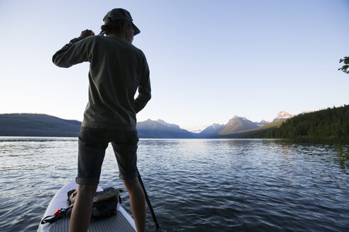 A woman stand up paddle boards (SUP) on Lake McDonald in Glacier National Park. - AURF03831