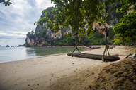 A wooden swing on the sand of Tonsai Beach in Krabi, Thailand with long tail boats in the background. - AURF03852