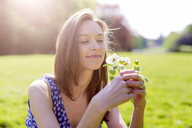 Smiling young woman in a park holding flowers - GIOF04281