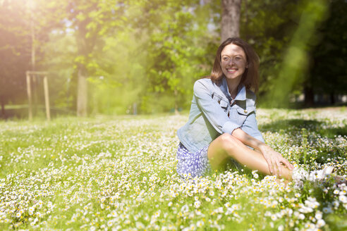 Smiling young woman sitting in a park - GIOF04284