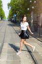 Young woman crossing a street with tramway tracks in the city - GIOF04287