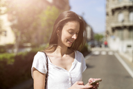 Smiling young woman looking at cell phone in the city - GIOF04290
