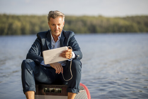 Portrait of relaxed businessman with earphones and tablet sitting on paddleboard at lake - FMKF05209
