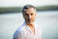 Portrait of mature man wearing wet white shirt at lake - FMKF05221