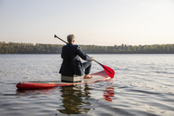 Back view of businessman paddling on lake - FMKF05224
