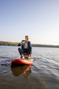 Businessman relaxing with drink on paddleboard on a lake - FMKF05227