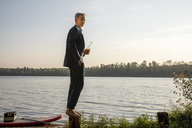 Businessman with beverage standing barefoot on a pole at lake - FMKF05230