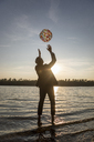 Silhouette of businessman standing at lakeshore by sunset throwing beach ball in the air - FMKF05233