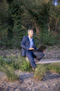 Mature businessman with laptop sitting barefoot in nature looking at distance - FMKF05236