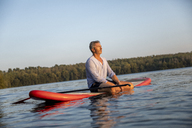 Mature man sitting on paddleboard on a lake by sunset relaxing - FMKF05239