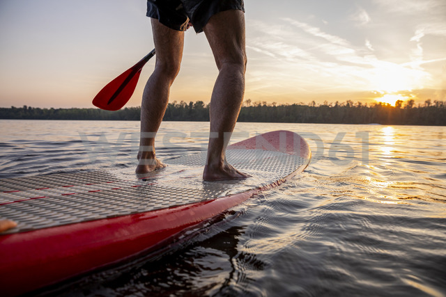Legs of man standing on paddleboard at sunset - FMKF05242