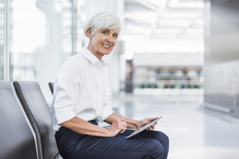 Smiling senior businesswoman sitting in waiting area using tablet - DIGF05017