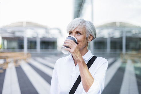 Senior businesswoman in the city drinking coffee - DIGF05029