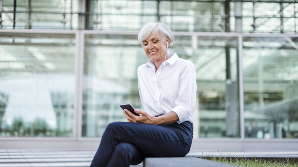 Senior businesswoman sitting outside with smartphone and earbuds - DIGF05038