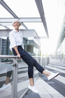Happy senior woman sitting on railing in the city looking around - DIGF05041