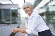 Portrait of confident senior woman leaning on railing in the city - DIGF05044