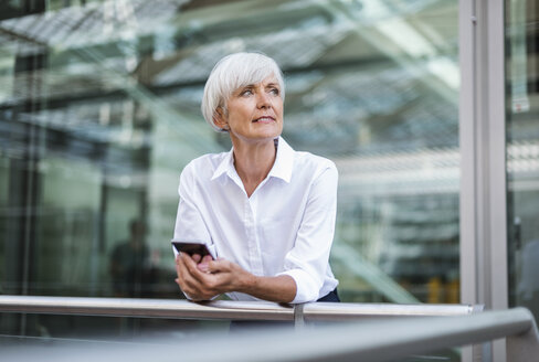 Senior businesswoman leaning on railing in the city with cell phone - DIGF05047