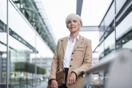 Portrait of confident senior businesswoman leaning on railing in the city - DIGF05050