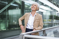 Smiling senior businesswoman leaning on railing in the city looking up - DIGF05053