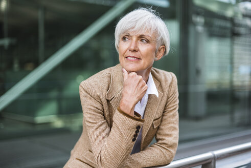 Portrait of senior businesswoman leaning on railing in the city looking around - DIGF05056