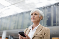 Senior businesswoman holding cell phone at the airport - DIGF05065