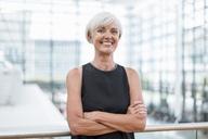 Portrait of smiling senior woman wearing black dress - DIGF05068