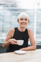 Portrait of smiling senior woman drinking a coffee - DIGF05077