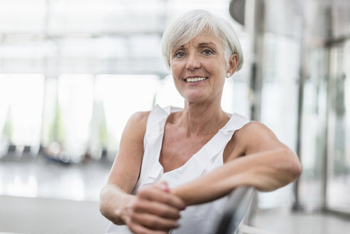 Portrait of smiling senior woman sitting in waiting area - DIGF05083
