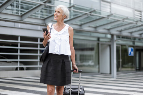 Smiling senior woman with cell phone and baggage on the move - DIGF05086