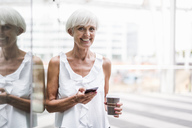 Portrait of smiling senior woman with cell phone and takeway coffee outdoors - DIGF05098