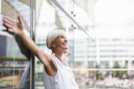 Happy senior woman leaning against glass facade with outstretched arms - DIGF05101