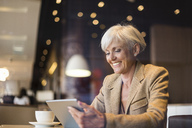 Smiling senior businesswoman using tablet in a cafe - DIGF05110